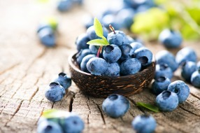 Freshly picked blueberries in wooden bowl. Juicy and fresh blueberries with green leaves on rustic table. Bilberry on wooden Background. Blueberry antioxidant. Concept for healthy eating and nutrition